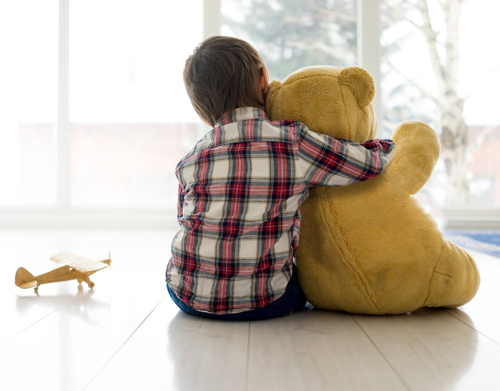 Little child sitting in living room with Teddy bear