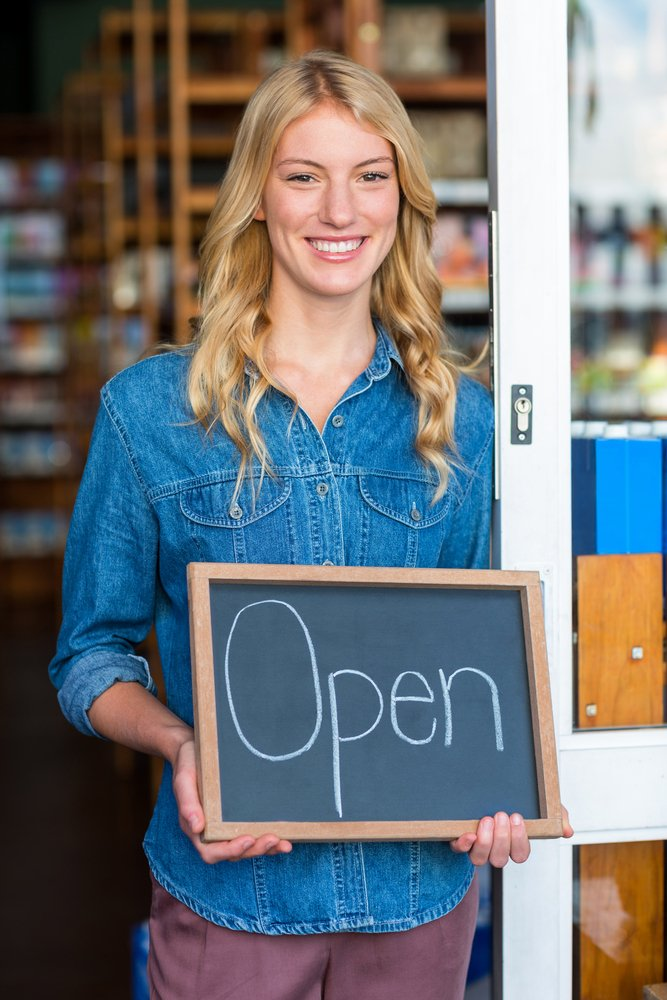 Portrait of smiling owner holding open sign